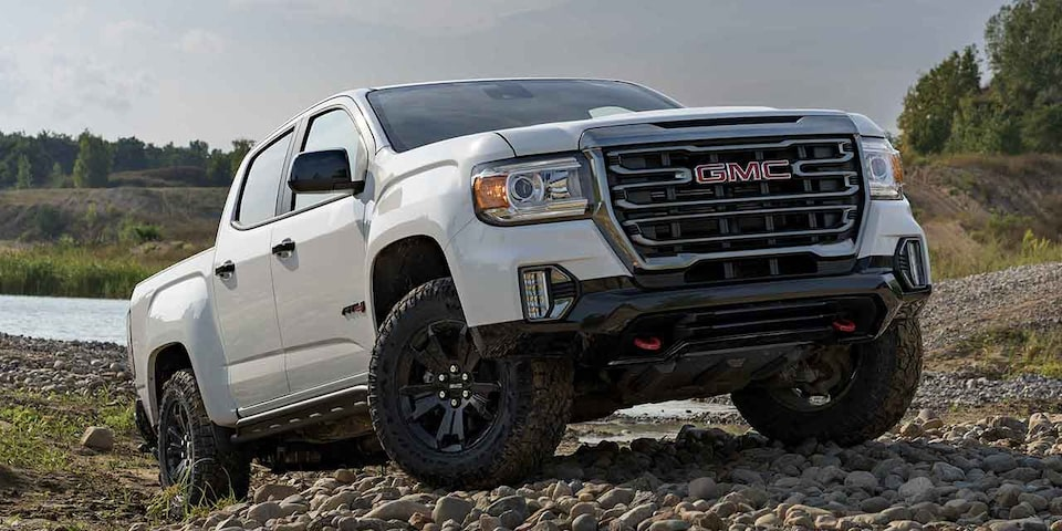 2021 GMC Yukon Denali driving on two-lane road through rugged terrain