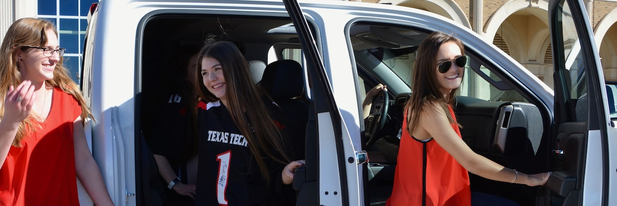 Photo showing a group of girls getting ready to tailgate inside their GMC Sierra pickup truck.