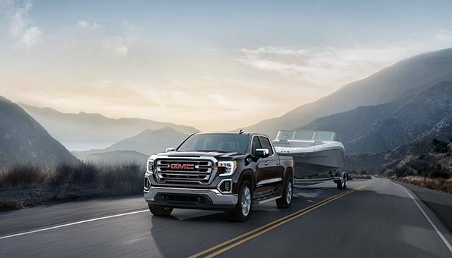 Photo of the next generation 2019 GMC Sierra 1500 light- duty pickup truck trailering a boat.