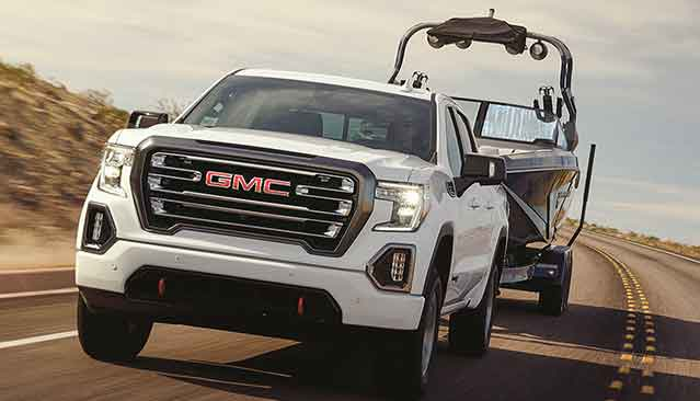 White GMC Sierra AT4 3L Duramax Diesel towing a boat on desert road - narrow view