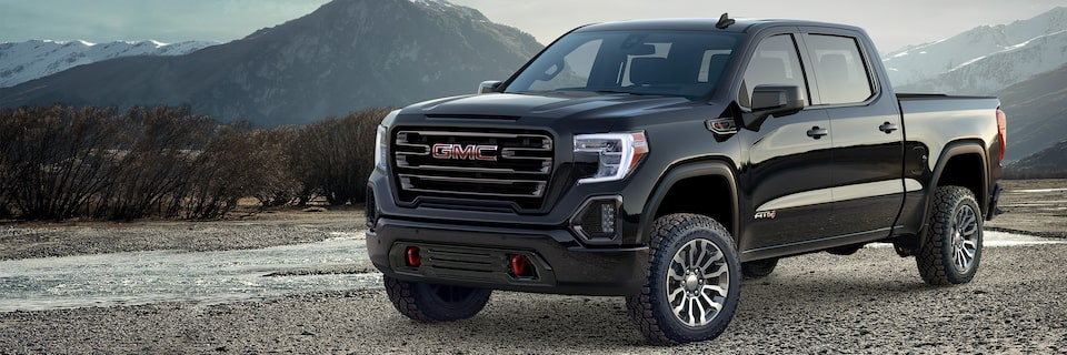 Image of the grille on the 2019 GMC Sierra 1500 light-duty pickup truck parked in a mountainous terrain.