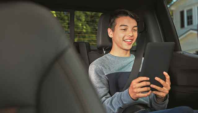 Smiling Child Using WarnerMedia Ride App on Compatible Device in GMC Vehicle
