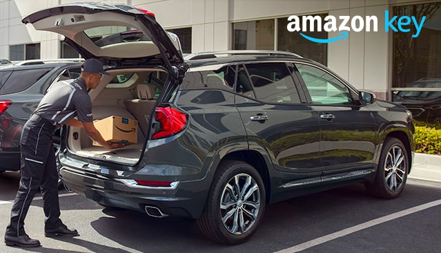 Image of a shipping employee inserting an Amazon package into the cargo area of a GMC vehicle.