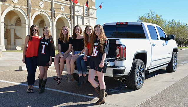 Photo of a group of girls tailgating with their GMC Sierra pickup truck.