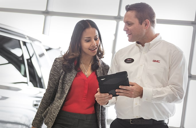 Image of a man and a woman discussing a vehicle at a GMC Business Elite Dealer.
