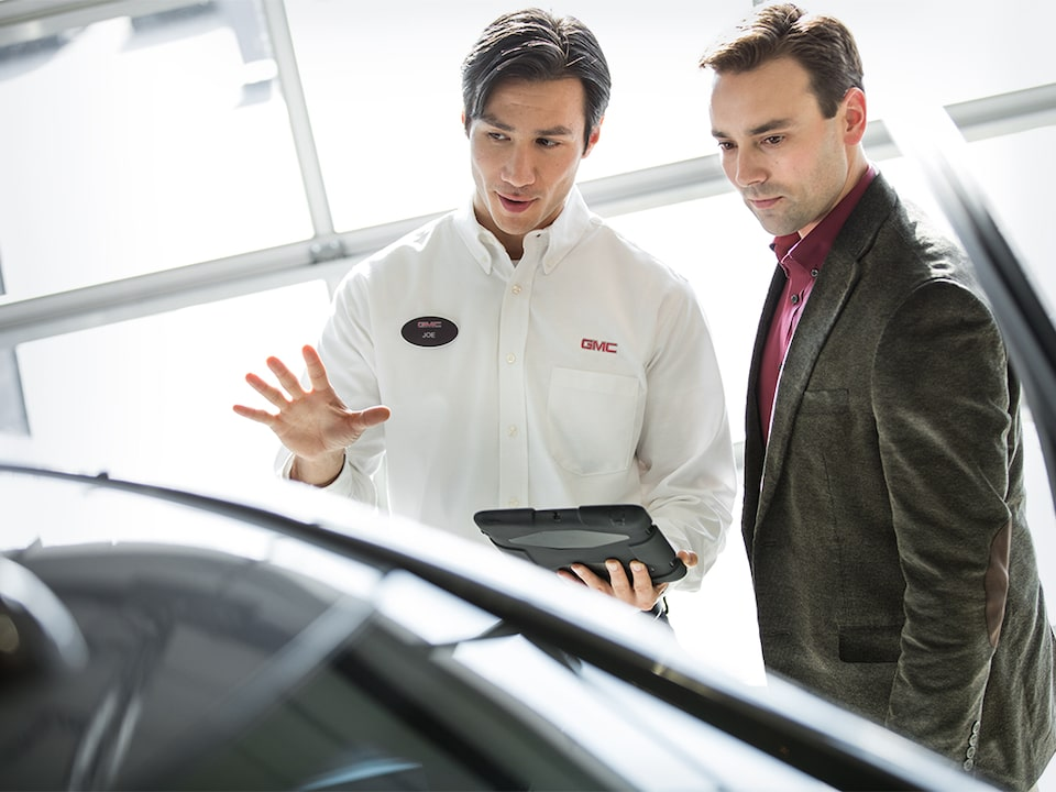 Image of two men discussing a vehicle at a GMC Business Elite Dealer.