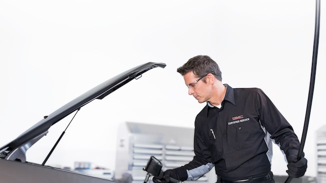 Image of a man delivering Certified Service to a GMC vehicle.