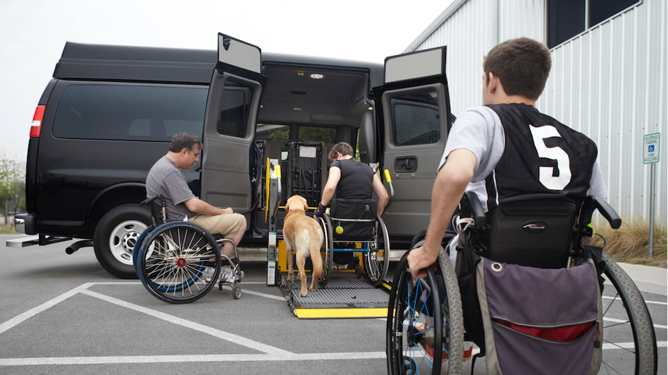 three men enters the 2020 GMC Savana Passenger Van using the wheelchairs friendly feature