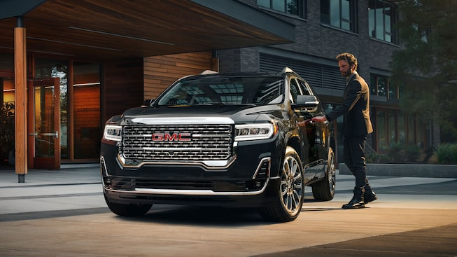 A man getting in the 2020 GMC Acadia Denali Luxury SUV