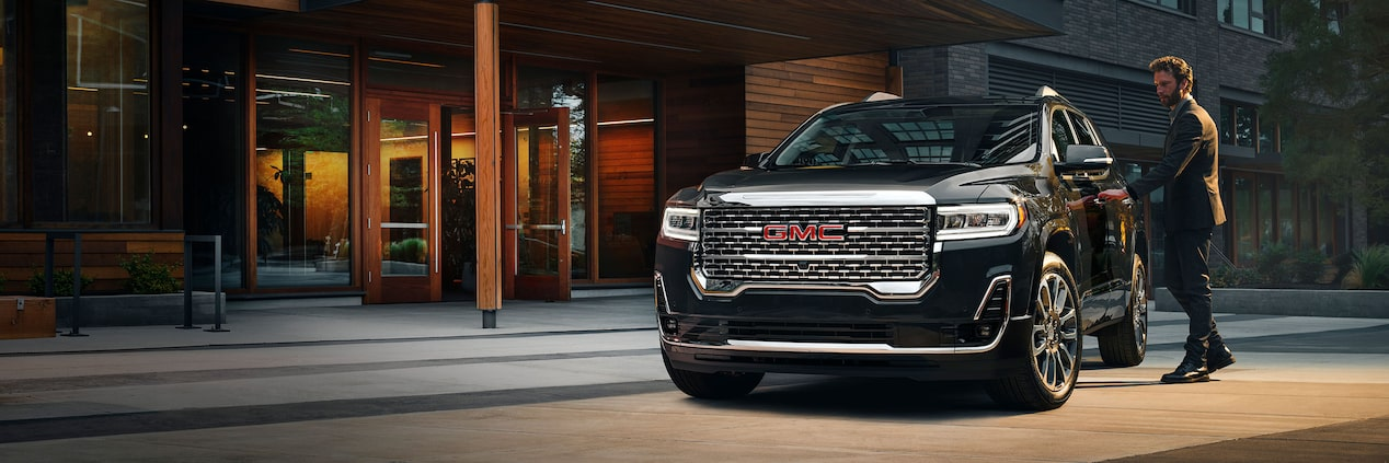 A man opening the door of the 2020 GMC Acadia Denali Luxury SUV