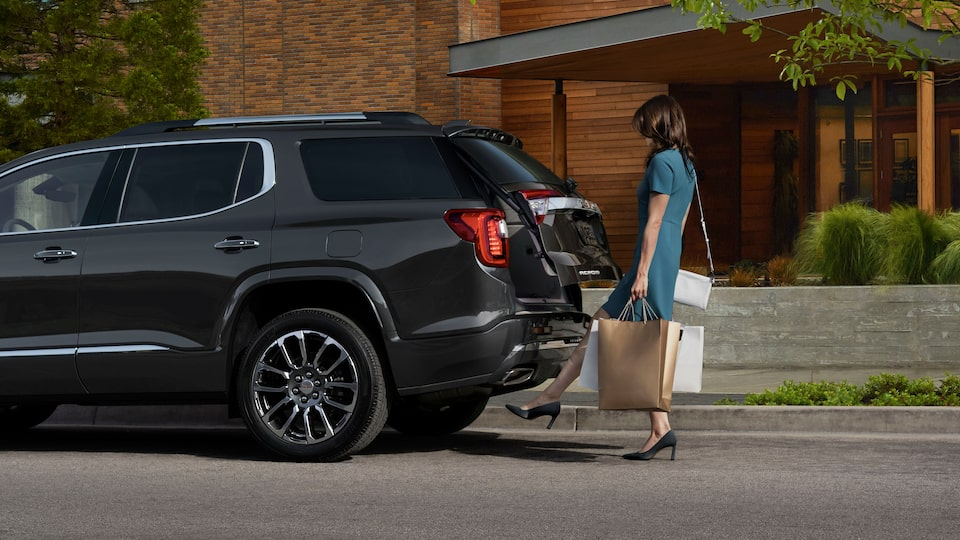 2020 GMC Acadia Denali Luxury SUV: A woman using her foot to activate a motion activated liftgate