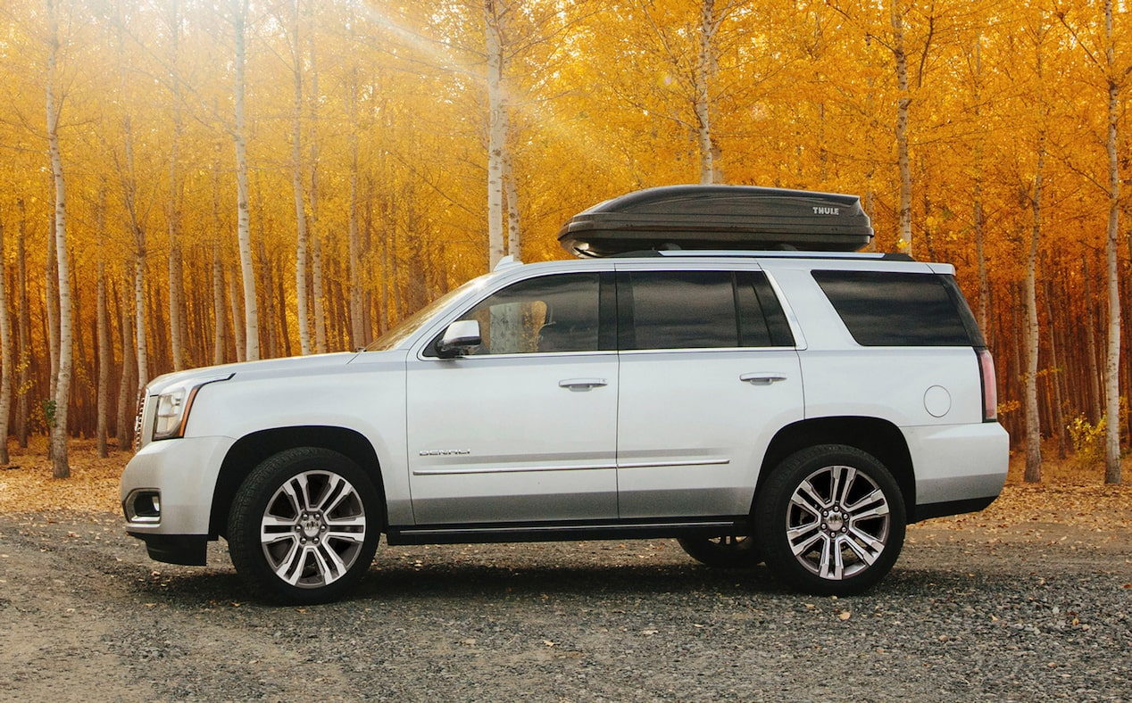 2020 GMC Yukon Denali Ultimate full size SUV side view with top carrier