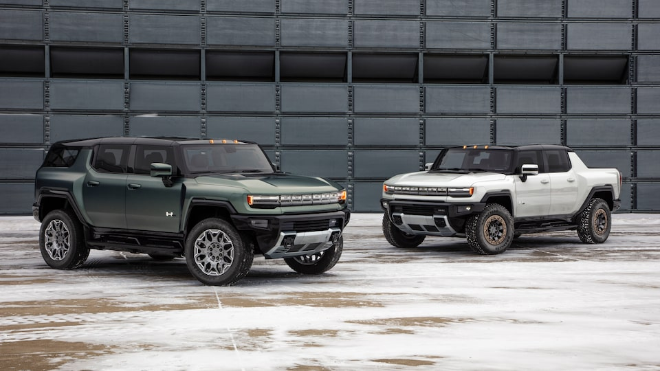 GMC HUMMER EV electric SUV and electric truck parked by building